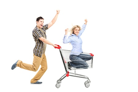 full shopping cart: Full length portrait of a young man pushing a woman in a shopping cart isolated on white background