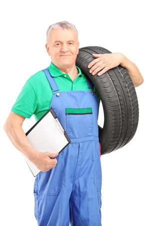 Mechanic holding a vehicle tire and a clipboard isolated on white background Stock Photo - 17495306