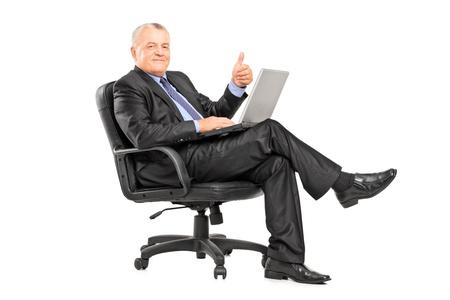 spokojený: Podnikatel sedí v křesle s notebookem a dává palec nahoru na bílém pozadí Reklamní fotografie
