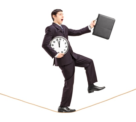 Full length portrait of a businessman holding clock and briefcase and walking on a rope isolated on white background photo