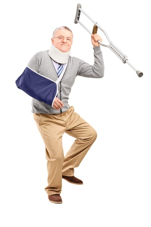 crutch: Full length portrait of a happy mature gentleman with broken arm holding a crutch isolated on white background