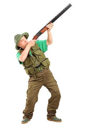 Full length portrait of a male hunter shooting with a shotgun isolated on white background