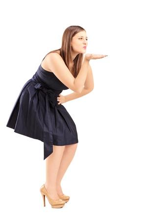 handkuss: Volle Länge Porträt einer jungen Frau bläst einen Kuss auf weißem Hintergrund