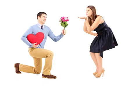 kneeling woman: Smiling male on knee giving a red heart and flowers to a woman blowing him a kiss isolated on white background