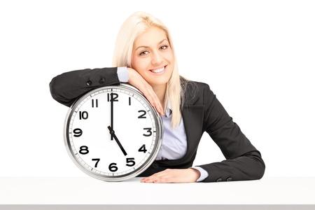 Jeune femme d'affaires assis avec une horloge murale, isolé sur fond blanc