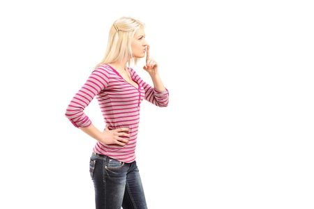 Young woman gesturing silence with finger over mouth isolated on white background