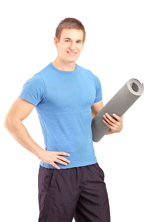 A male athlete holding a mat isolated on white background photo