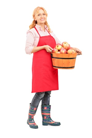Full length portrait of a woman with apron holding a bucket full of apples isolated on white background photo