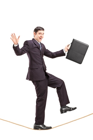 steadiness: Full length portrait of a young businessman with briefcase walking on a rope isolated on white background Stock Photo