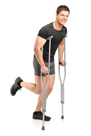 Full length portrait of an injured young male athlete walking with crutches isolated on white background photo