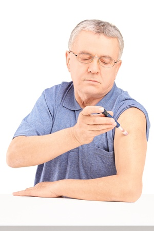 Mature man sitting and injecting insulin in his arm isolated on white background photo