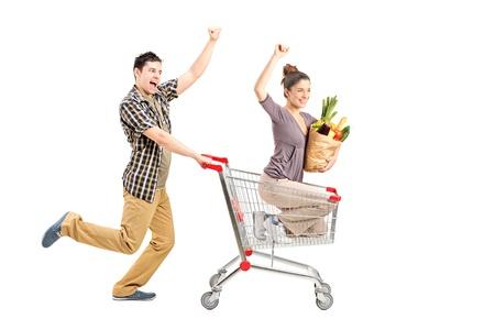 hombre empujando: Joven pareja feliz de las compras, el hombre empujando un carrito de la compra aislados en fondo blanco