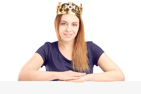 A beautiful queen with a golden crown posing behind a blank panel, isolated on white background photo