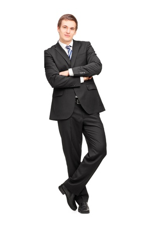 leaning: Full length portrait of a young businessman leaning against wall isolated on white background