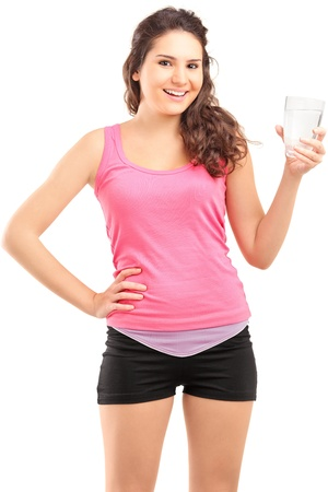 Sportswoman holding a glass of water isolated on white background photo