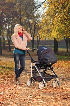 baby stroller: Young mother talking on a mobile phone during a walk in the park with her baby in a pushchair