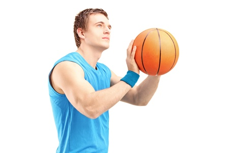 A young basketball player shooting basketball isolated against white background photo