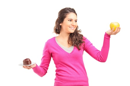 Doubtful woman holding green apple and cake and trying to decide which one to eat photo