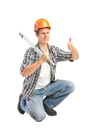 A smiling worker holding a construction bubble level and giving thumb up isolated on white background Stock Photo - 17588715
