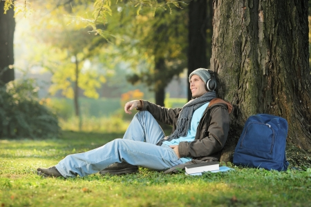 A male student relaxing and listening music seated on a grass in the city park Stock Photo - 17588712