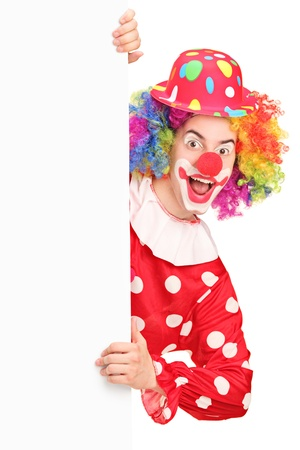 A smiling male clown posing behind a blank panel isolated on white background Stock Photo - 17588713