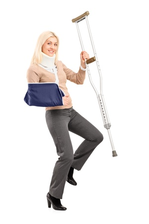 Full length portrait of a happy blond female with broken arm holding a crutch isolated on white background Stock Photo - 17591049