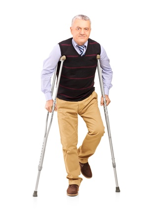 Full length portrait of a happy gentleman walking with crutches isolated on white background Stock Photo - 17591046