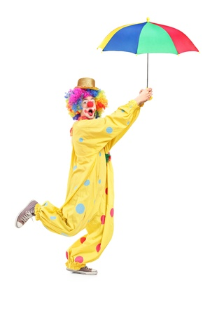 Full length portrait of a male clown with umbrella isolated on white background photo