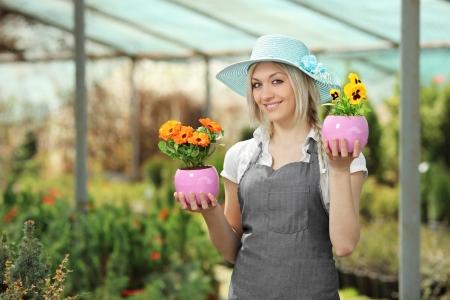 Young female gardener holding flower pots in a garden Stock Photo - 17588714
