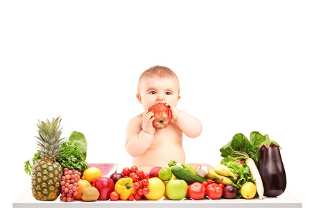 Cute baby boy sitting on a table with fruits and vegetables and eating an apple isolated on white background