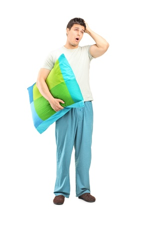 late 20s: Full length portrait of a young man in pijamas feeling sleepy isolated on white background