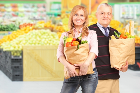 Man and woman in a supermarket holding paper bags with groceries photo