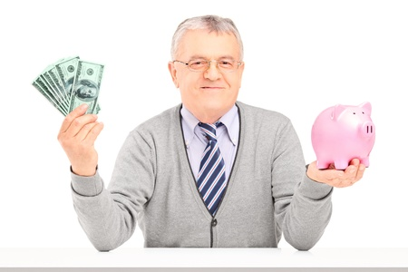 Mature man sitting, holding money and a piggy bank isolated on white background photo