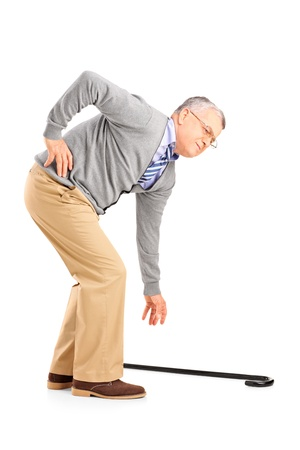 stiff: Full length portrait of a senior man with back pain trying to pick up a cane isolated on white background