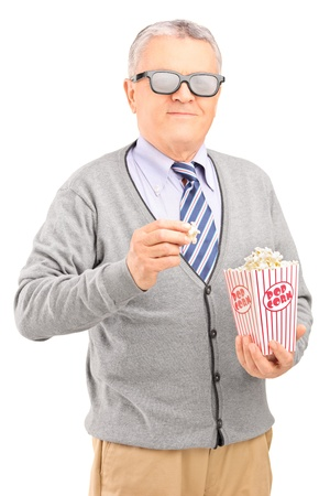 eating popcorn: Mature gentleman eating popcorn isolated on white background