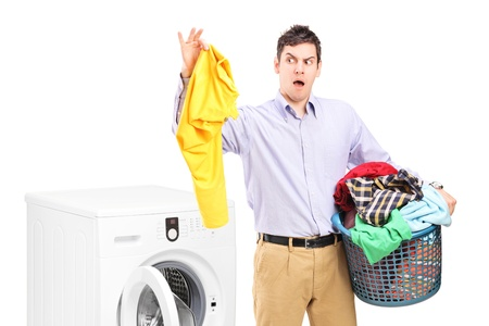 smelly: Young man standing next to a washing machine and holding dirty laundry isolated on white background