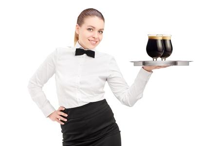 sirvientes: Una camarera con la pajarita que sostiene una bandeja con dos vasos de cerveza oscura en él aislados en fondo blanco