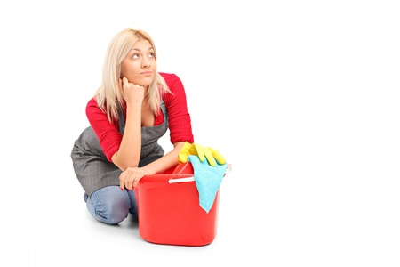sitting on floor: Exhausted female cleaner sitting next to a bucket isolated on white background