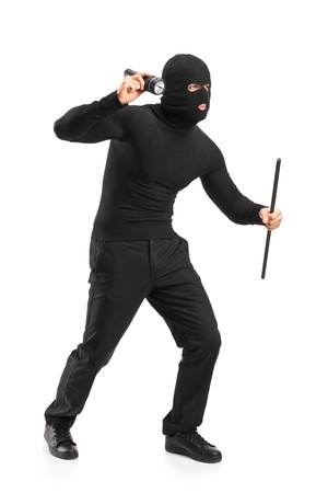 Full length portrait of a robber with mask holding a flashlight and piece of pipe isolated on white background photo