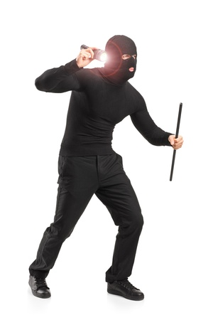 Full length portrait of a robber with robbery mask holding a flashlight and piece of pipe isolated on white background photo