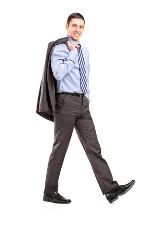 Full length portrait of a young businessman walking with a coat over shoulder isolated on white background photo