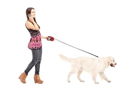 In voller Länge Portrait einer jungen Frau zu Fuß mit ihrem Hund und sprechen über ein Handy isoliert auf weißem Hintergrund Standard-Bild