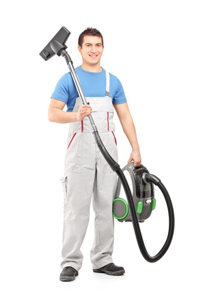 vacuuming: Full length portrait of a young male worker holding a vacuum cleaner isolated on white background Stock Photo