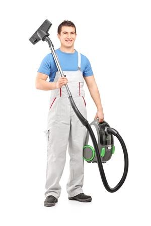 gospodarstwo domowe: Pełna długość portret młodego pracownika męskiej trzyma odkurzacz na białym tle
