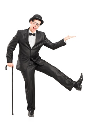 full suit: Full length portrait of a young performer in black suit holding a cane and dancing isolated on white background