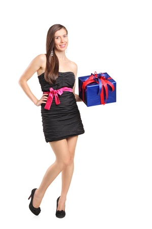 Full length portrait of an attractive smiling woman holding a gift isolated on white background photo