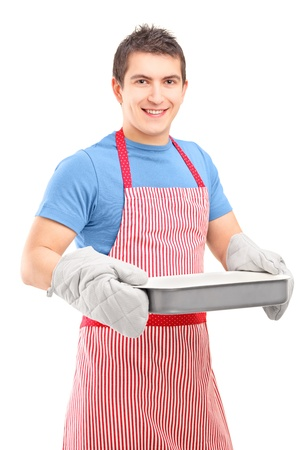 dinner wear: Smiling guy wearing cooking mittens and apron holding a baking tray isolated on white background
