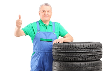 A mature worker posing on car tires and giving thumb up isolated on white background Stock Photo - 17784763