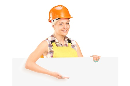 Female manual worker standing behind blank panel and gesturing isolated on white background Stock Photo - 17784764