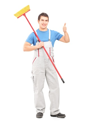 Full length portrait of a male painter holding a roller and giving a thumb up isolated against white background